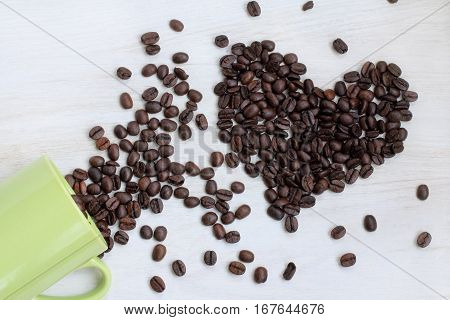real fried coffee beans spilled on a table in the shape of a heart top view / sort your favorite