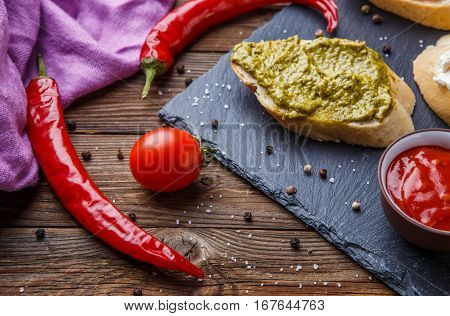Photography of snacks with vegetables on black plank on wooden table