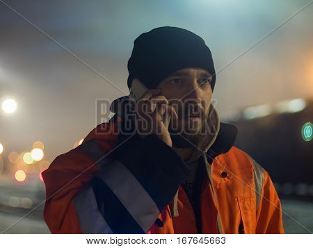 Worker talking by smartphone bokeh light in bacground. Concept of night shift.