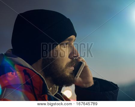 Man talking by smartphone at night bokeh light in background.
