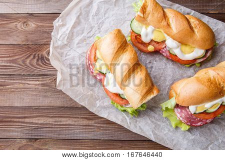 Fresh sandwiches with sausage and vegetables on paper at wooden table
