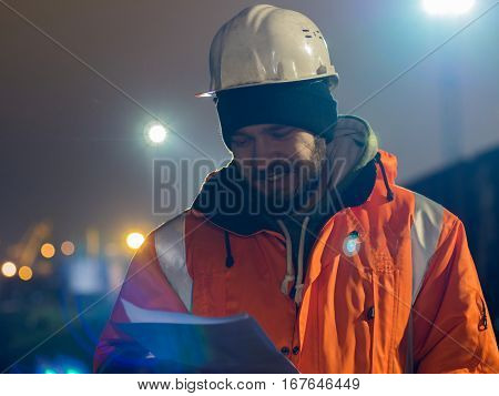 Portrait of young and happy construction worker in helmet at night.