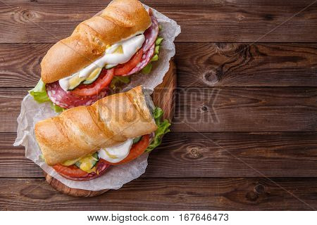 Appetizing baguette with sausage and vegetables on wooden table