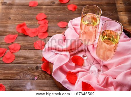 Festive evening with glass of champagne, rose petals