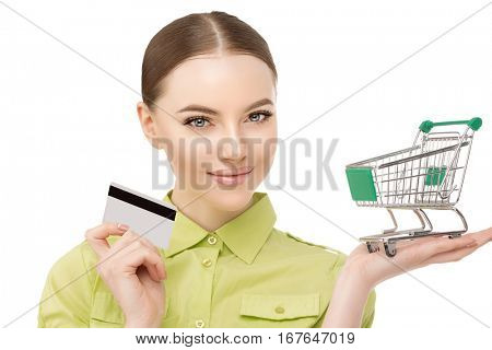 Woman with a trolley for shopping bags and credit bank card in his hand. A woman make purchases at the mall.