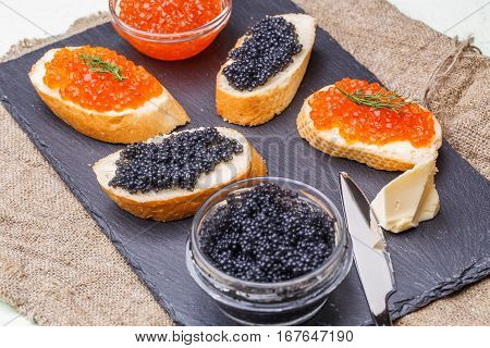 Photo of baguette with black and red caviar, knife, cup on blackboard