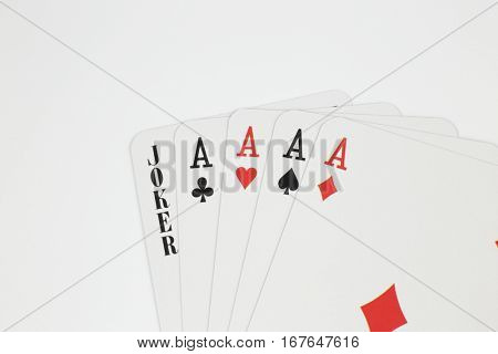 Playing cards - four aces and joker close up isolated in studio. poster