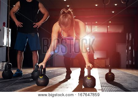 Group of adults doing exercises with kettle bells. Cute blonde girl doing push ups in gym. Fitness, sports concept.