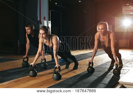Group of muscular caucasian adults exercising with kettle bells in gym. Weightlifting, power lifting workout. fitness, sports concept.