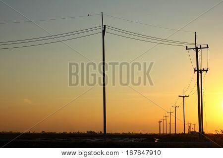 Power line pole on the dirt road in the field