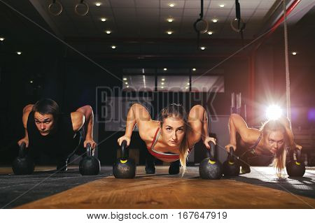 Young muscular athletes doing push up exercise with kettlebell equipment. Weightlifting, power lifting workout. Fitness, sports concept.