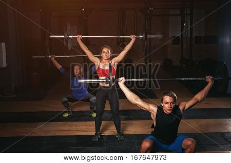 Group of sporty young adults exercising with barbells in gym. Three muscular people doing squats with weight over the head. Sports, fitness concept.