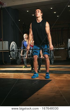 Group of sporty adults exercising with barbells in gym. Young athletes doing dead lift exercise with weight. Fitness, sports concept.