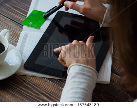 Close-up Woman shopping online with credit card and tablet.