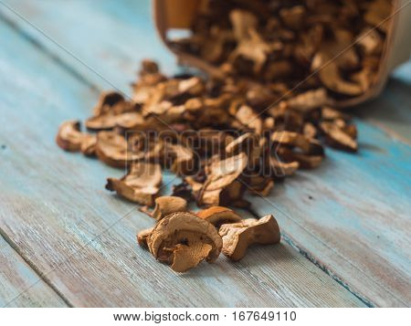 forest mushrooms dried in a basket on wooden table, side view.