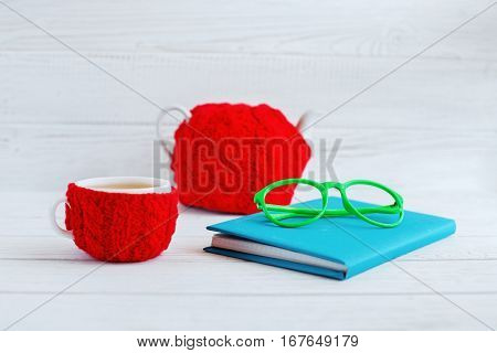 .The book glasses a cup of tea and teapot on a white background. The concept of learning and work.