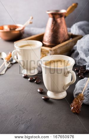 Two retro cups of coffee and old coffee pot on dark brown background with copy space.