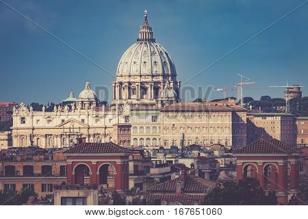 St. Peter Vatican City, Rome - Italy. Aerial. Morning. The dome of St. Peter view from the side. Lights, sky, no clouds. Suggestive atmosphere. View from Villa Borghese in Rome.