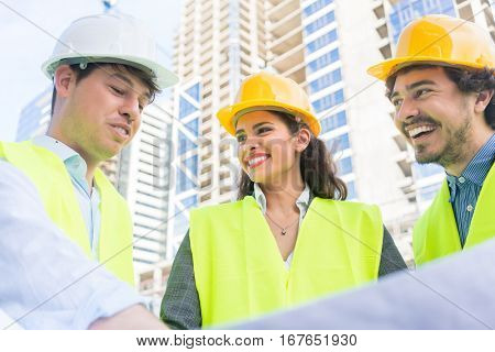 Architects and civil engineers with ground plot on construction site of highrise building