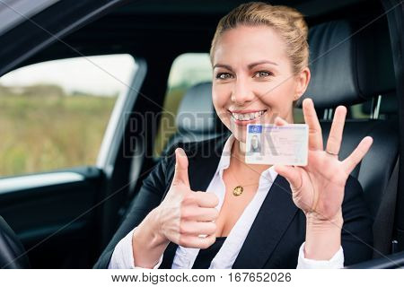 Woman showing driving license and thumbs up