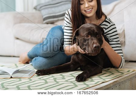 Fell my love. Delighted smiling pretty lady giving her cute little pet a hug while lying on a carpet with a book and enjoying her weekend