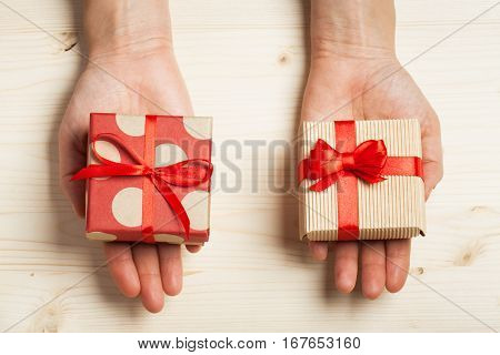 Two hands holding gifts in kraft boxes with a bows on a wooden background.Surprise your loved one. The concept of the day of St. Valentine's Mother's Day birthday New Year Christmas and other holidays. Flat fly.