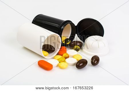 Colored Capsules, tablets and pills in a plastic jar. Studio Photo