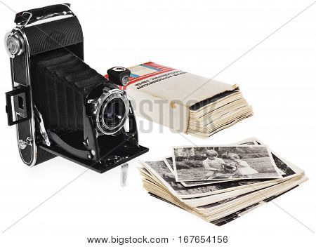 Composition of: - Antique black pocket camera, open ready for use. - Retro black and white photographs of two children and a dog - Old white cardboard box on photo paper - Historic negative for the camera