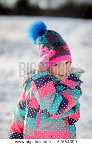 Winter portrait of girl of younger school age. Child is warmly dressed in a bright motley jacket and a cap. Mittens on hands. Girlie corrects a cap. Against the background of snow.