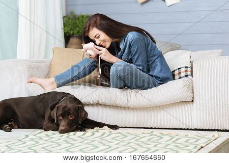 Cutest model ever. Elegant creative stunning girl using a light pink camera taking pictures of her pet while sitting on a cozy sofa beside him