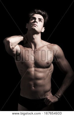 Sexy young man shirtless. Gym muscular body. He has a hand behind his head. Muscular body, hes a well-defined. He looks up and seems almost aching neck. Black compact background
