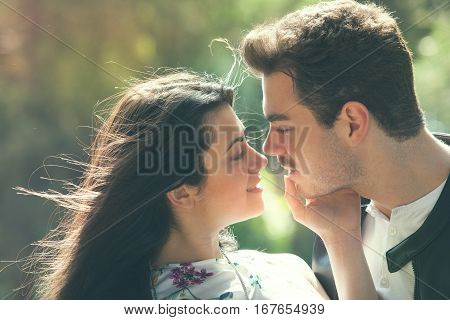 Couple love feeling. Loving harmony. First kiss. Caresses and kisses. A young men and a young woman. Attitude romantic and sentimental. The two lovers caressing their cheeks and approach for kissing. Outdoors.