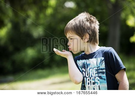 Playing boy on lawn. Funny white child with baseball cap. Young lad boy sends a kiss. Youngster with thoughtful face. In captivity of activity. Son spends leisure time activities in house garden.