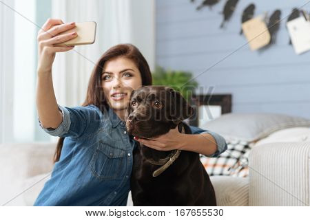 Look on the screen. Charming emotional young lady using her smartphones front camera taking a snap of herself with her best friend memorizing the moment