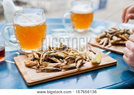 Fried small fish anchovy on board and beer on a blue table in the bar with a nautical theme. Spending fun time with great food.
