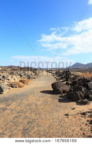 Gravel road running through dry landscape on Lanzarote