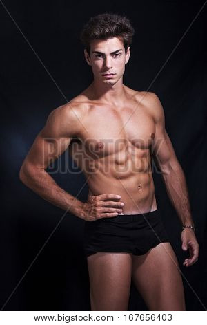 Great, muscular and beautiful young man model in underwear posing in studio. On black. He has a statuesque body and its appearance is truly beautiful. Wearing a black box underwear.