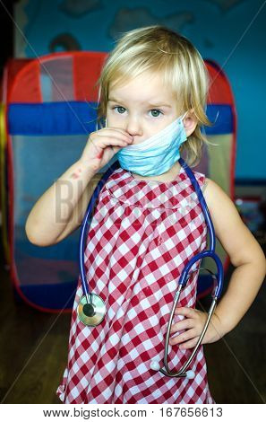 Little girl playing doctor with her doll. A child dressed in a surgical mask and a stethoscope in his hand.