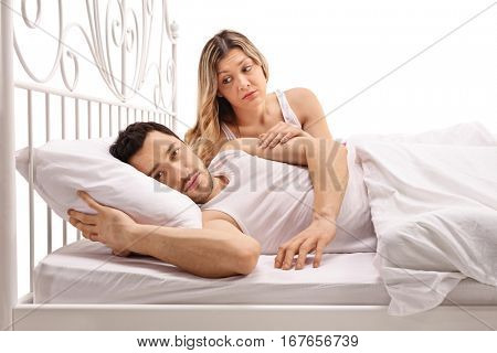 Unhappy man lying in bed with a concerned woman comforting him isolated on white background