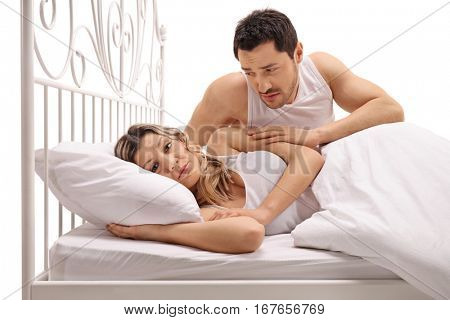 Unhappy woman lying in bed with a concerned guy comforting her isolated on white background