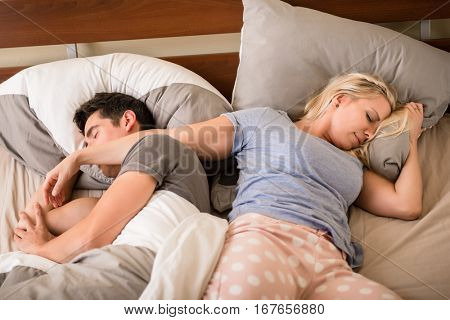 High-angle view of young man and woman sleeping back-to-back in bed