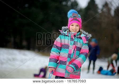The girl of younger school age has come to the winter park to drive on the sheet sledge. It is snowing. The girl warmly is also brightly dressed. She has a good mood.