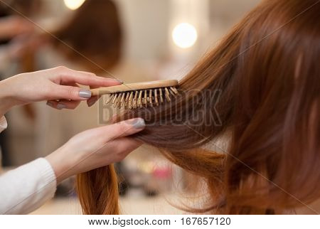 Hairdresser combing her long red hair of his client in the beauty salon. Professional hair care and creating hairstyles.
