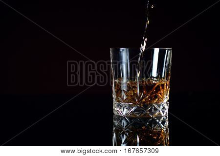 Pouring Bourbon whiskey into glass. Black table with beautiful reflection.