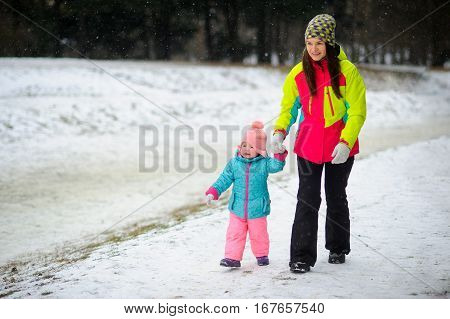Young mother has brought the little daughter into the winter park. Both are dressed in bright warm ski suits. The woman holds the baby by a hand. It is snowing. Baby for some reason cries.