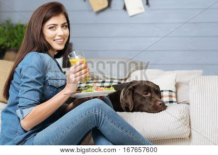 Bright start of the day. Magnificent joyful slender girl enjoying her healthy breakfast while sitting on the floor near the couch where her adorable pet lying