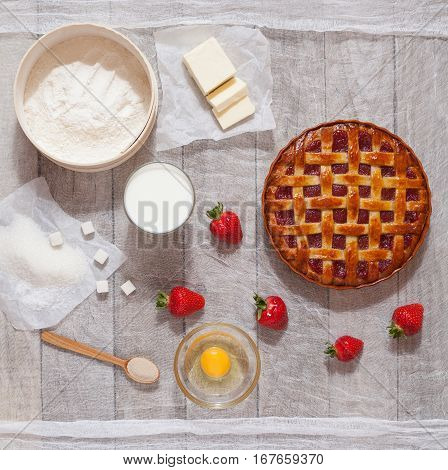 Traditional homemade strawberry pie tart cake sweet baked pastry food with the ingredients of which it is a bright kitchen table. Flat lay.