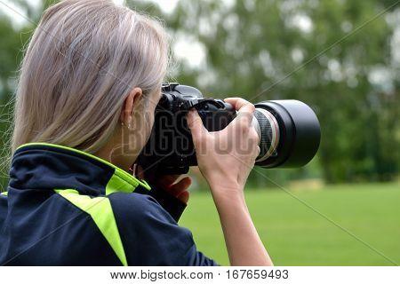 Woman photographed with big camera - closeup