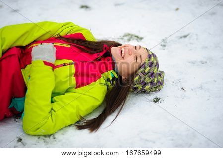 The charming young woman lies on snow. She is dressed in a bright jacket and a knitted cap. The woman rejoices to winter and snow. She cheerfully laughs.