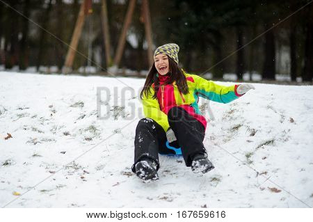 The young woman cheerfully moves down from a hill on the saucer sled. The first snow has slightly covered the earth. The woman in a bright ski suit with pleasure spends the day off in the winter park.